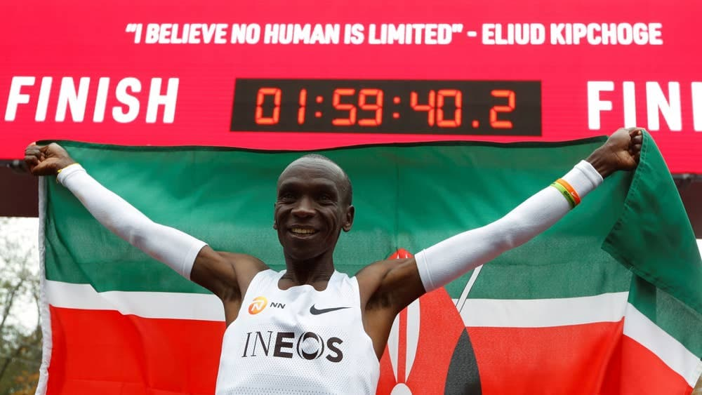 Eliud Kipchoge posando con la bandera de Kenia y el cronometro que marca menos de dos horas
