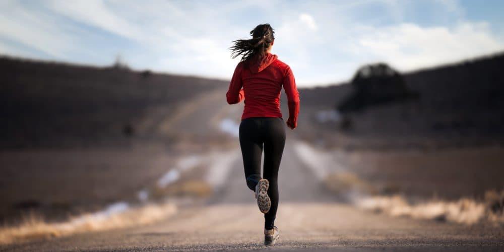 Mujer corriendo en carretera desierta