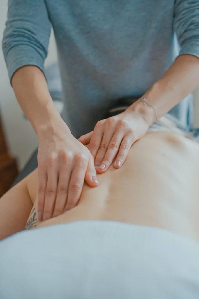 Persona aplicando punto de presión en espalda baja